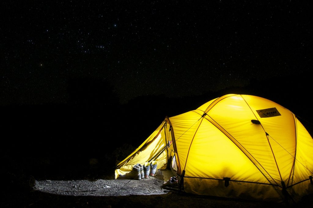 Internally lit tent at night. Hiking boots at the entrance