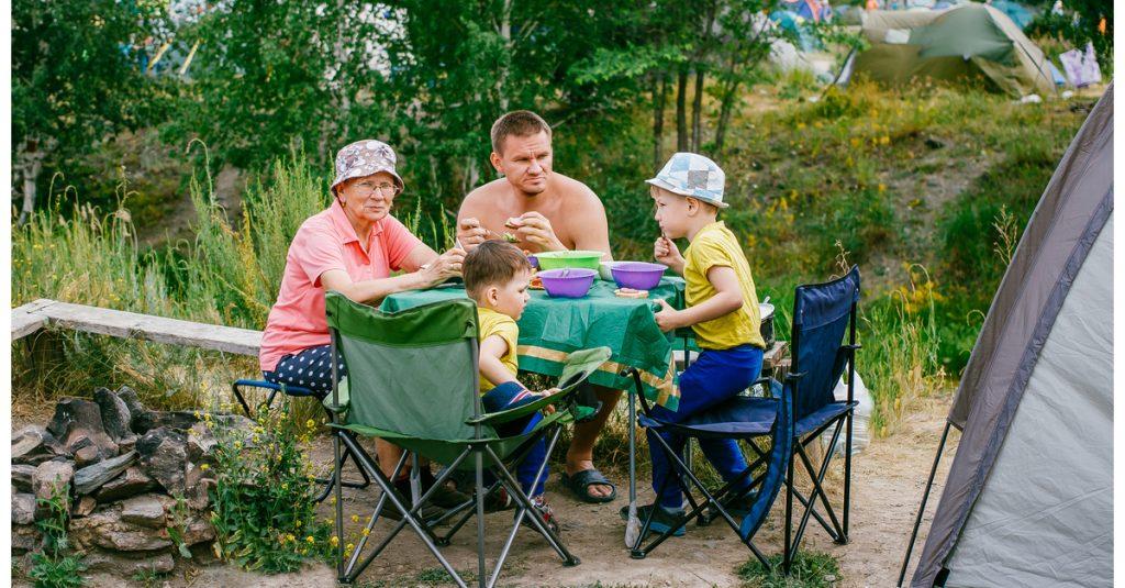 Family Sitting at Folding Table and Chairs