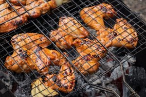 Buffalo wings cooking over barbeque in grill basket