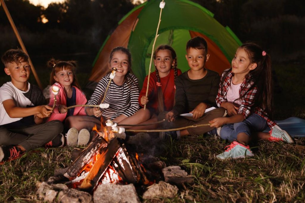 Happy Children Camping and cooking smores on campfire.  Family camping tent requirements are only one concern