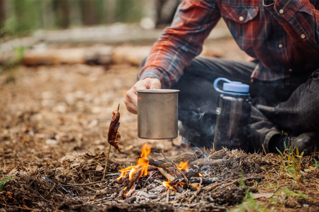 Making coffee in mug over small campfire