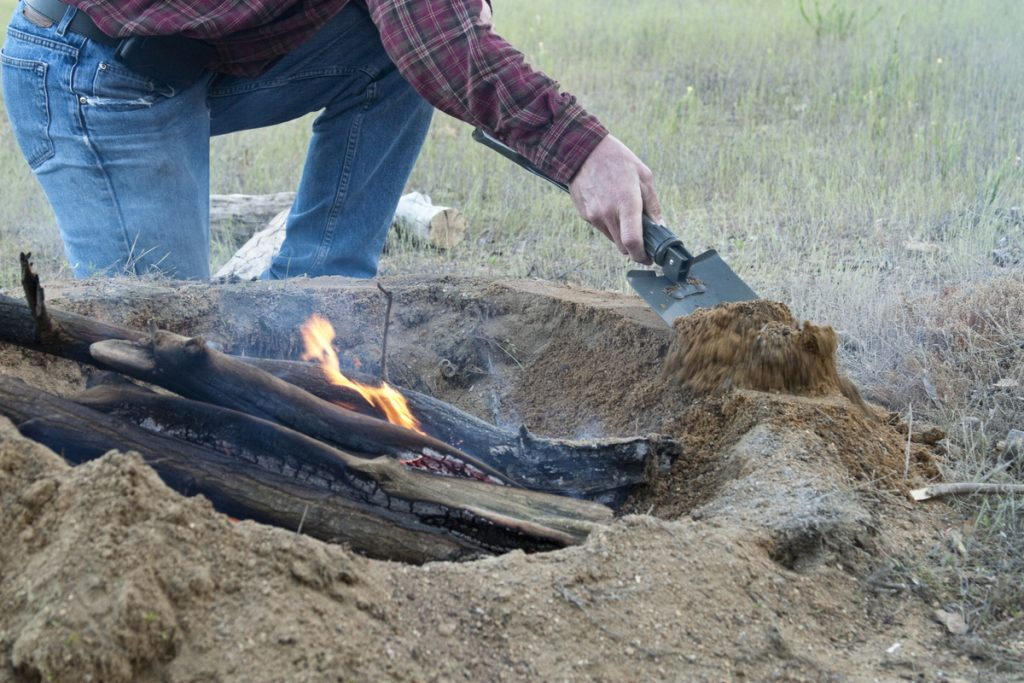 Man building robust fire ring from soil