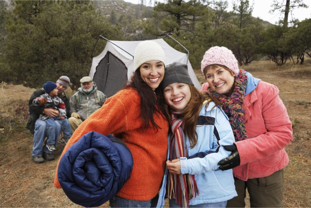 Family in front of a tent wearing Fleeces, gloves and woolly hats