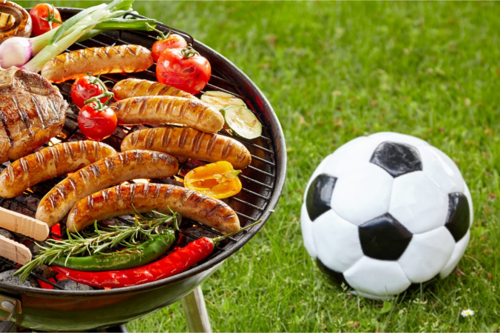 Barbeque grill laden with food.  Soccer ball sitting on ground