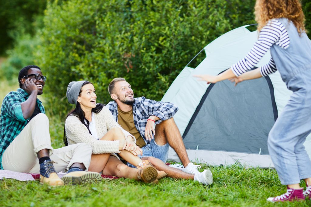 4 adults playing charades in front of a tent