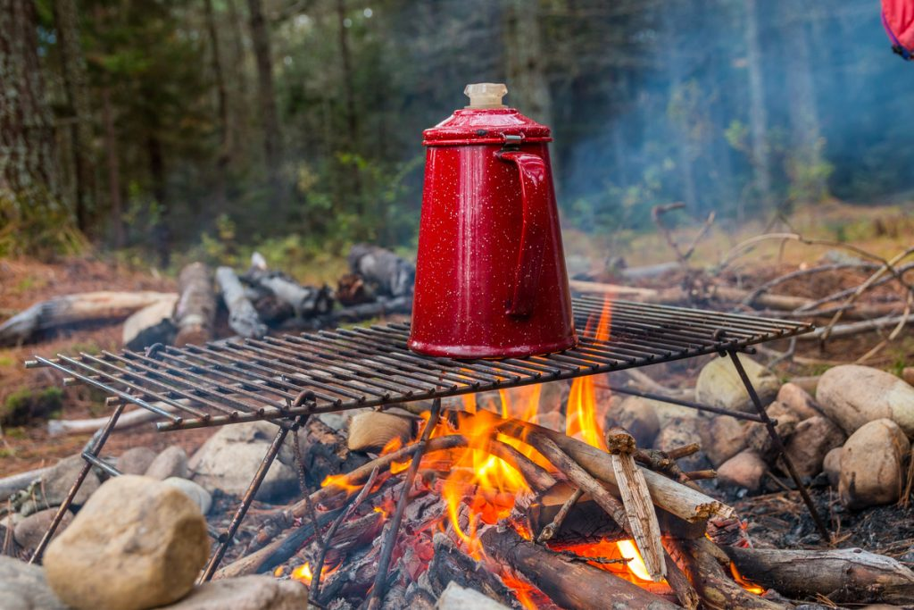 Red coffee pot on a grill rack over an open campfire.  This is the traditional way to make great coffee while camping