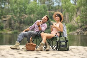 Happy couple relaxing on camping chairs