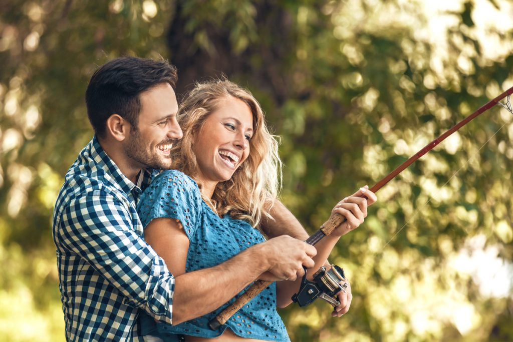 2 young adults laughing while fishing
