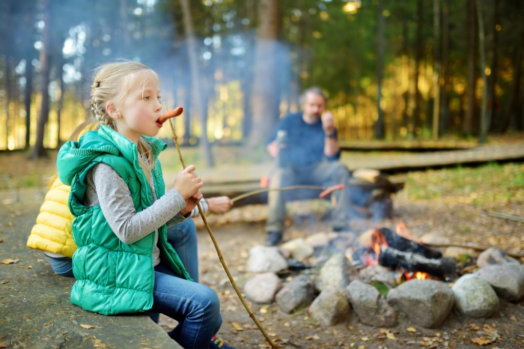 Girl eating hotdog sausage she has roasted over the campfire