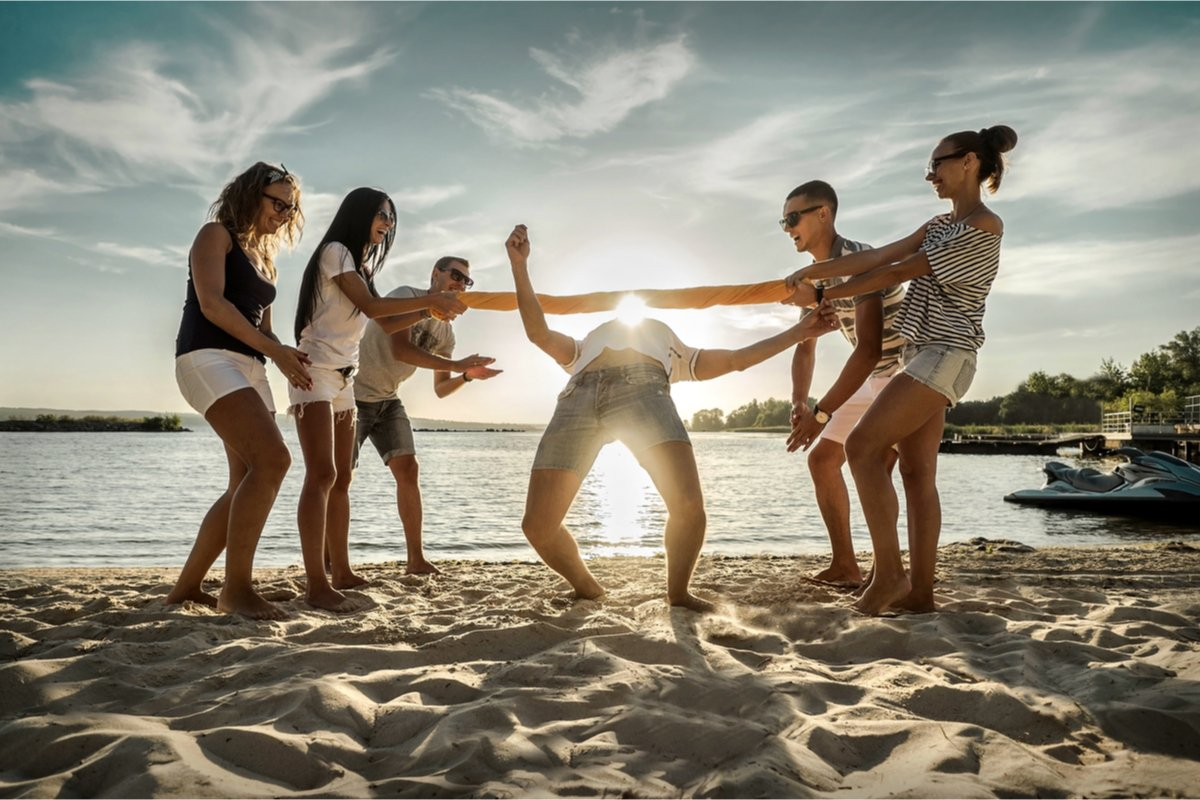 Camping Activities for Adults - Group of Friends With an Impromptu Limbo Game on the Beach