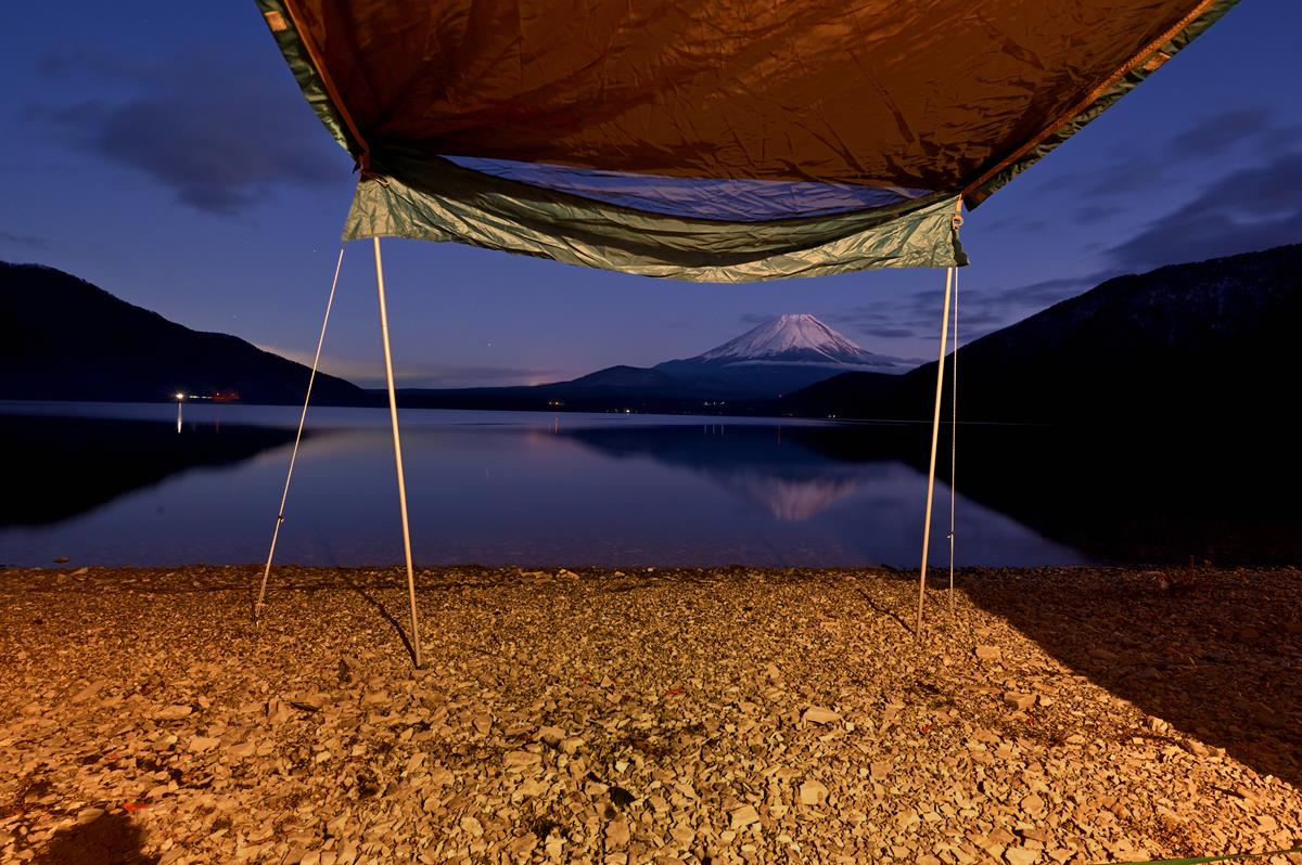 Looking out over a lake from underneath a camping tarp