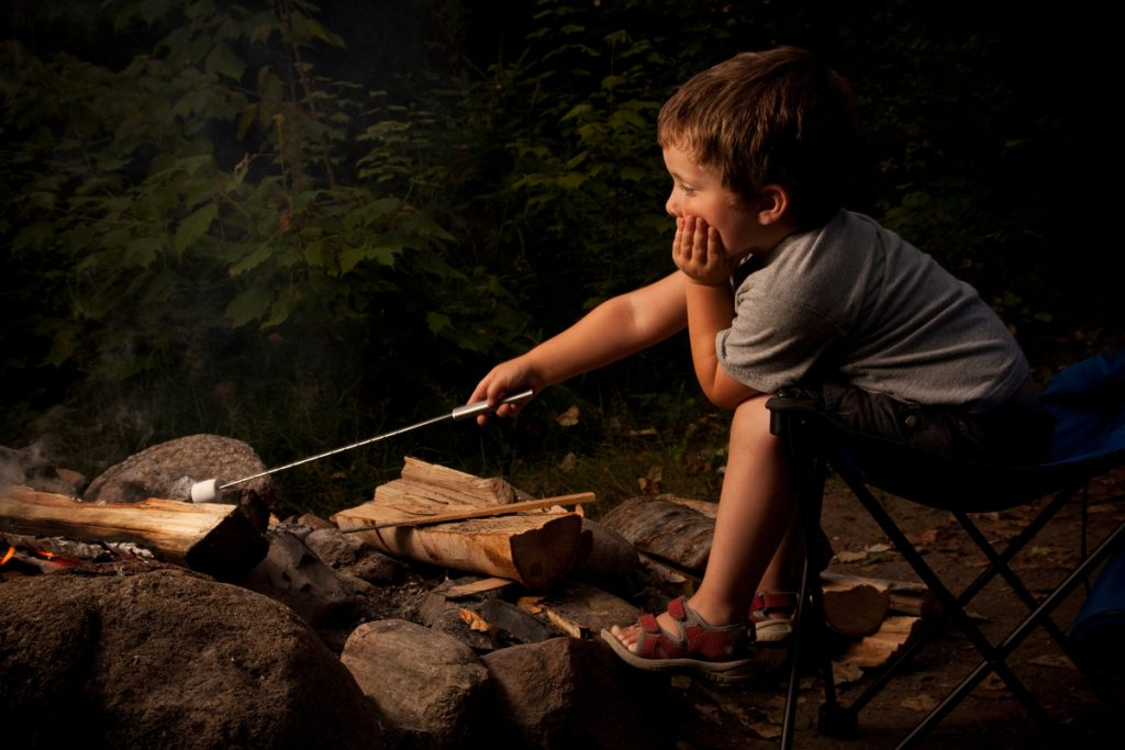 Young boy trying to roast a marchmallow over small campfire