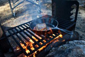 Succulent Steak in a pan over a campfire
