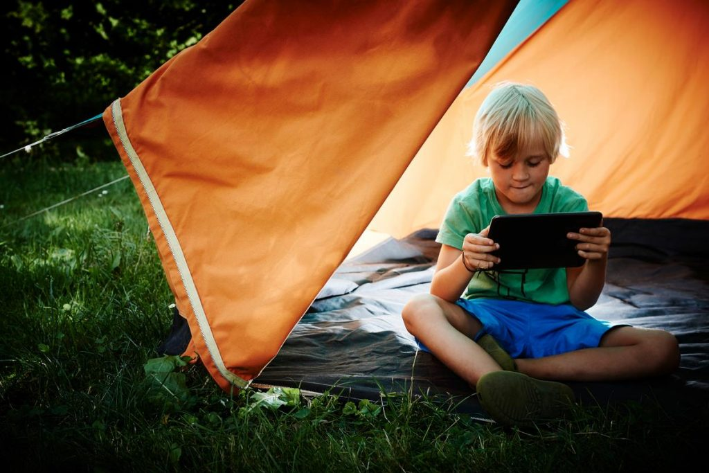 boy in lit tent avidly looking at a tablet computer