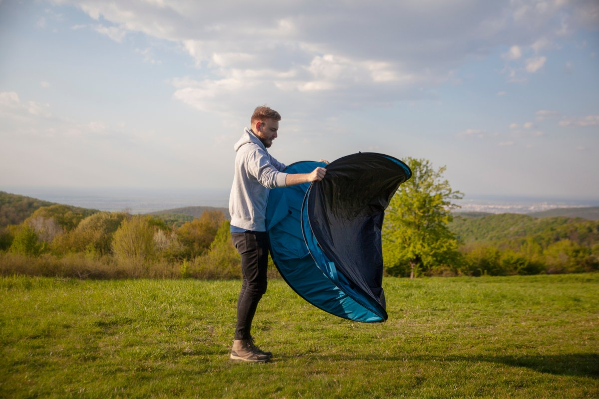 Man releasing a pop up tent