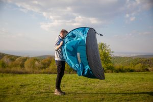 Man opening pop up tent. Do pop up tents come with pegs