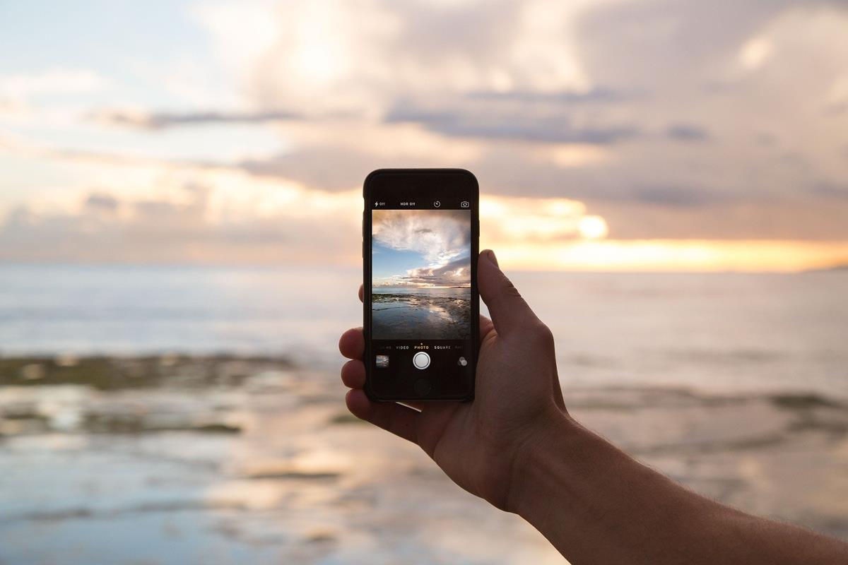 Photograph of a smartphone taking a picter of a beautiful lakeside scene